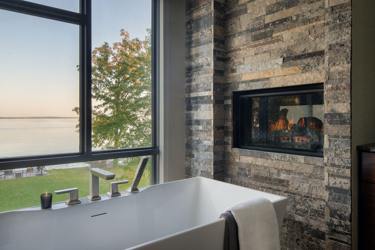 close up of bathtub with fireplace in bathroom